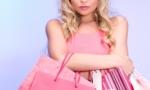 un mujer rubia llena de bolsas de comrpa
